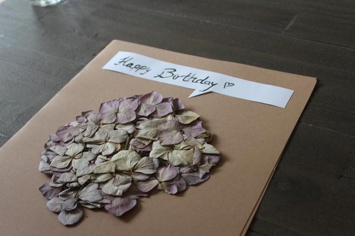 Geburtstagskarte-aus-Packpapier-und-einer-getrockneten-Blume-Hand-im-Glück-