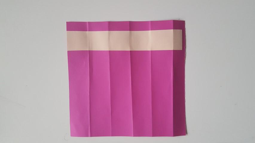 Streifen-Papier-auf-die-pinke-Fläche-kleben-Stiftgeschenkverpackung-zur-Einschulung-Hand-im-Glück