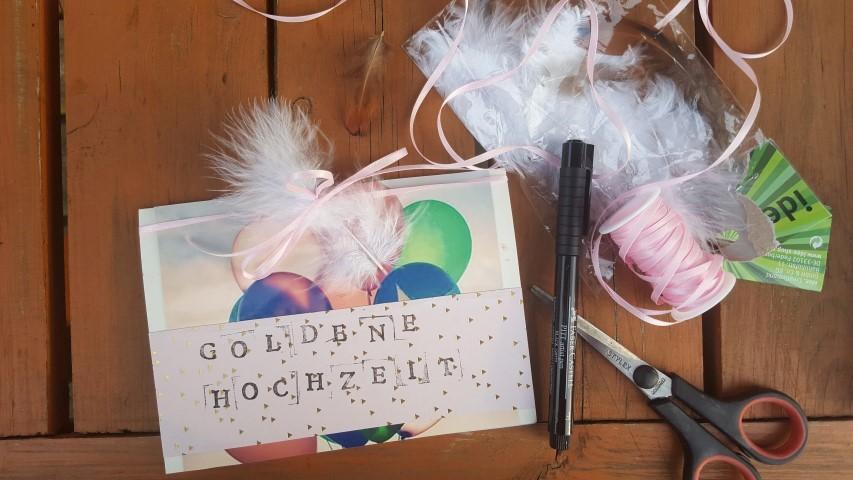 Glückwunschkarte-Goldene-Hochzeit-mit-Schleife-und-Federn-schmücken-Hand-im-Glück