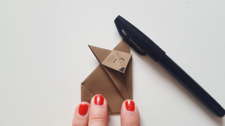 Origami Fuchs Schritt 11 Mund und Augen mit einenn schwarzen Stift anmalen Hand im Glück