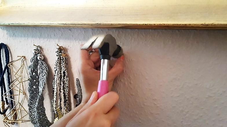Schmuckaufhänger-Nägel-in-die-Wand-mit-dem-Hammer-hämmern-Hand-im-Glück.