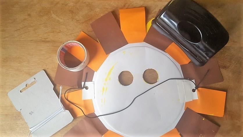 Löwen-Maske aus Pappteller Gummiband befestigen Hand im Glück