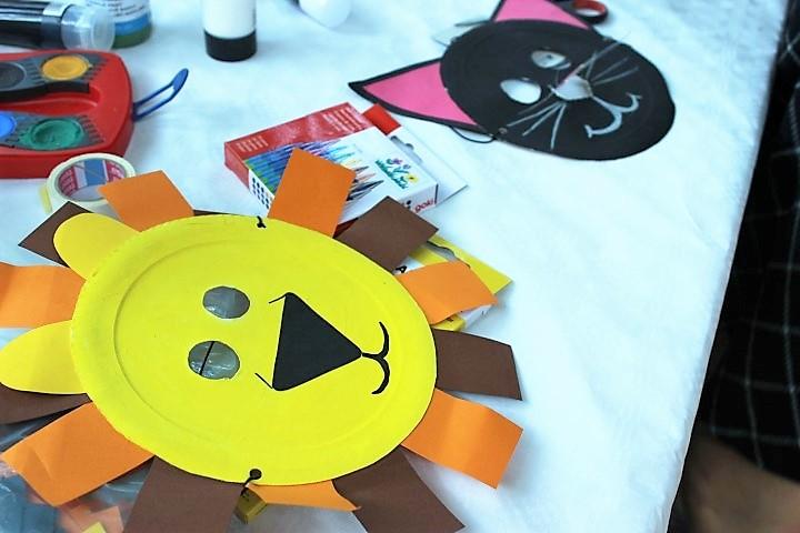 Löwen-Maske aus Pappteller auf dem Tisch Kinderfest Hammer Park Hand im Glück