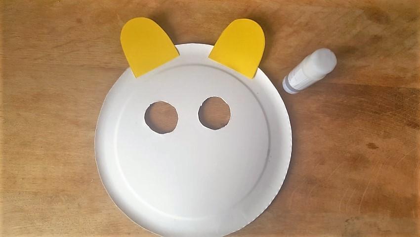 Löwen-Maske aus Pappteller gelbe Ohren von hinten ankleben Hand im Glück
