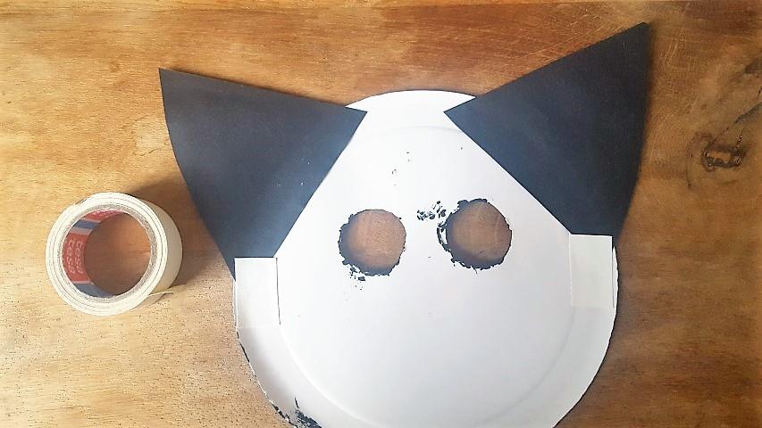 Maske-aus-Pappteller-Katze-Klebeband-von-hinten-an-die-Maske-kleben-Hand-im-Glück