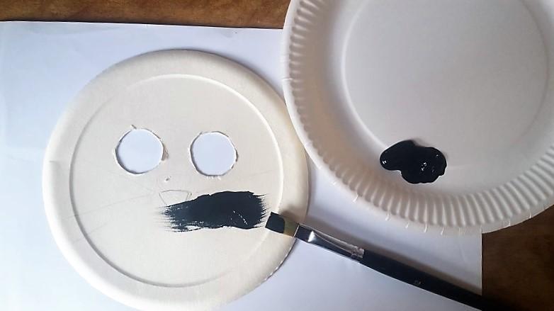Maske-aus-Pappteller-Katze-Pappteller-schwarz-anmalen-Hand-im-Glück