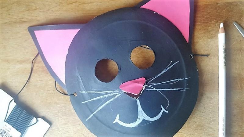 Maske aus Pappteller Katze mit einem weißen Stift Munf und Schnurhaar malen Hand im Glück