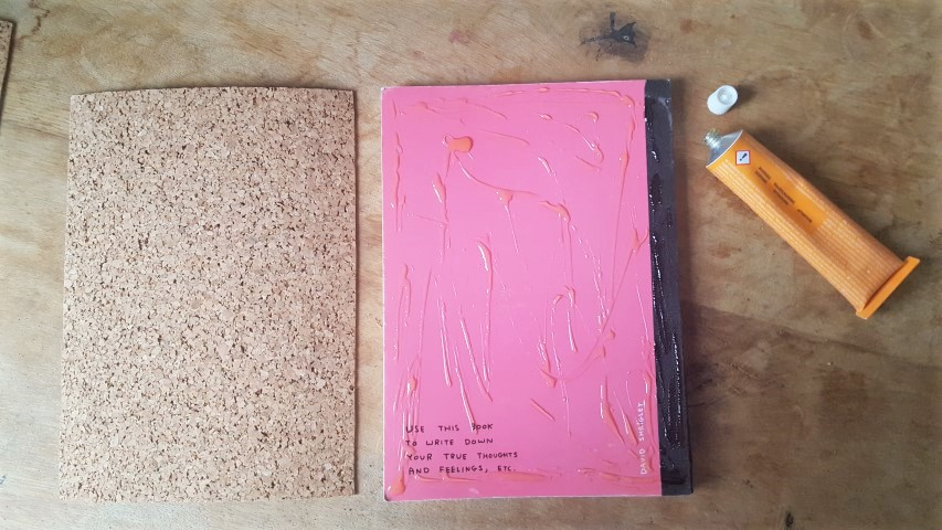 Notizbuch mit Korkumschlag und Textilband Kork auf das Notizbuch kleben Hand im Glück