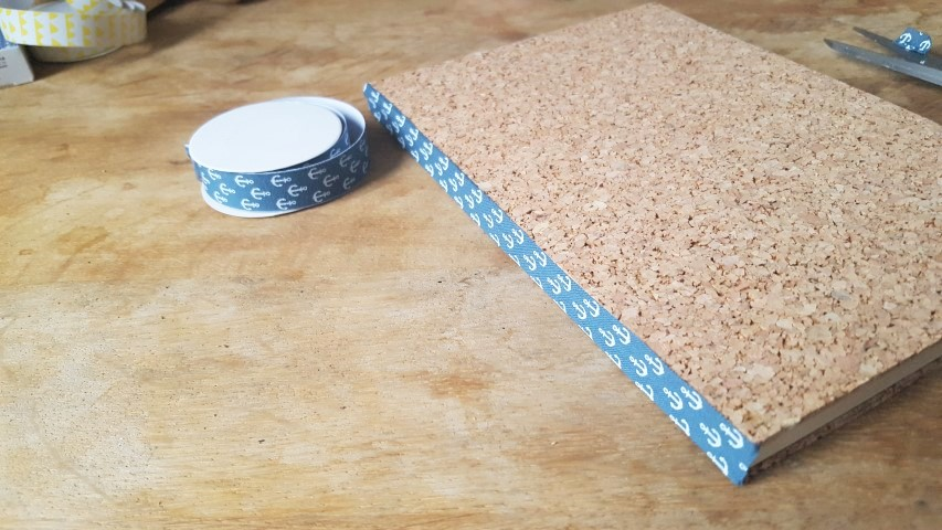 Notizbuch mit Korkumschlag und Textilband an der Seite anbringen Hand im Glück