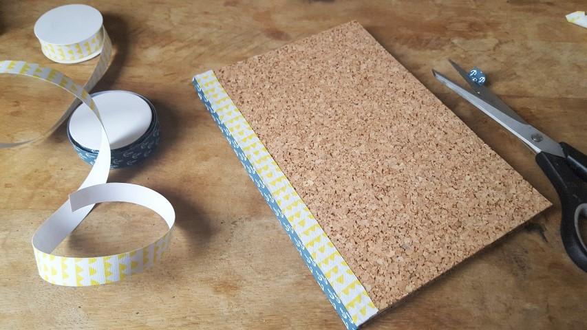 Notizbuch mit Korkumschlag und Textilband gelbes Textilband ergänzen Hand im Glück