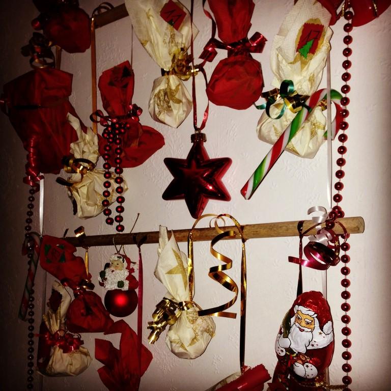 Adventskalender aus hängender Leiter aus Holzstäben und Bändern