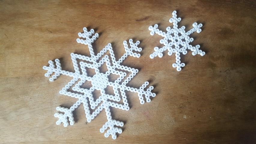 Schneeflocken aus Bügelperlen große und kleine Schneeflocke beim abkühlen Hand im Glück