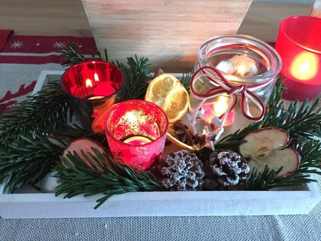 Weihnachtsgesteck mit roten Glasteelichtern Hand im Glück