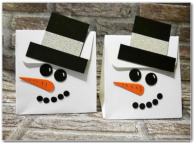Schneemanntasche aus Papier gebastelt als Geschenk im Winter Hand im Glück