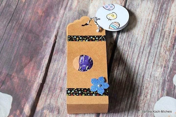 Geschenkanhänger für Schokoladenosterhasen aus Papier Hand im Glück